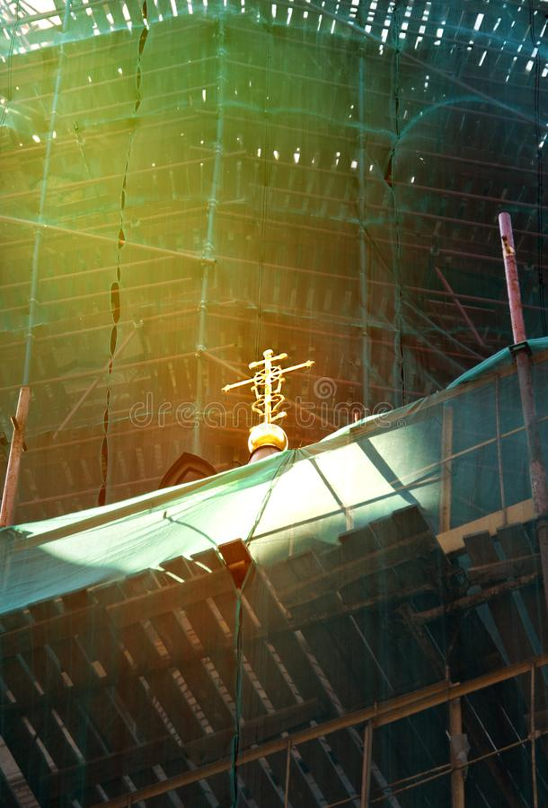 A ray of light on the cross of an Orthodox church during repair time. A ray of light on the cross of an Orthodox church, scaffolding during repair time stock image