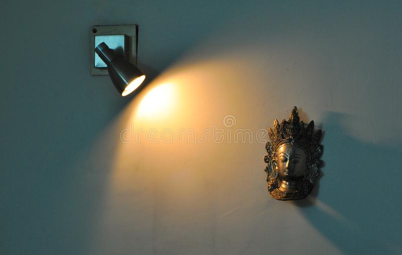 Ray of light falling on a wall show piece. Yellow-ray-of-light, musk, wall-hanging, brick-wall, white-wall, metal-show-piece, tungsten-bulb, electric, indoor stock image