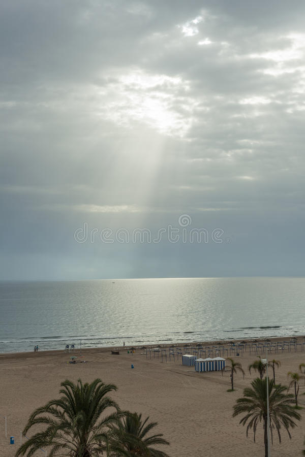 Ray of sun through the clouds lighting the horizon line between. Sky and sea royalty free stock photo