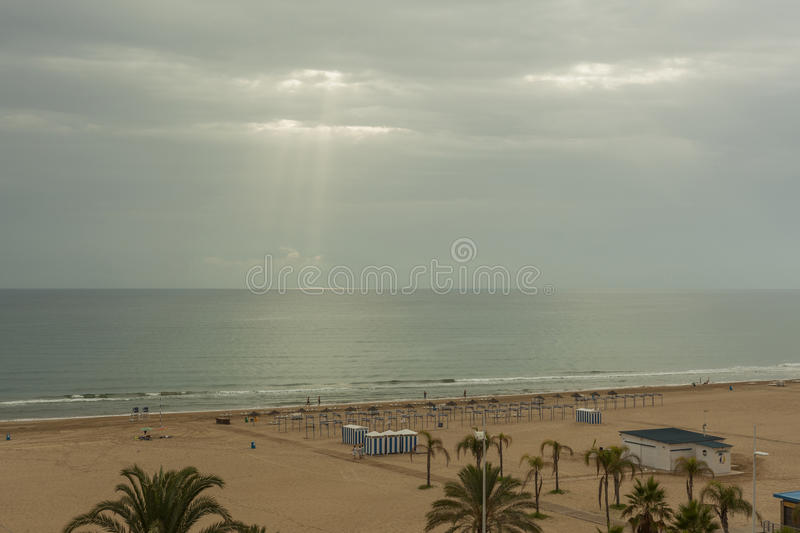Ray of sun through the clouds lighting the horizon line between. Sky and sea stock image