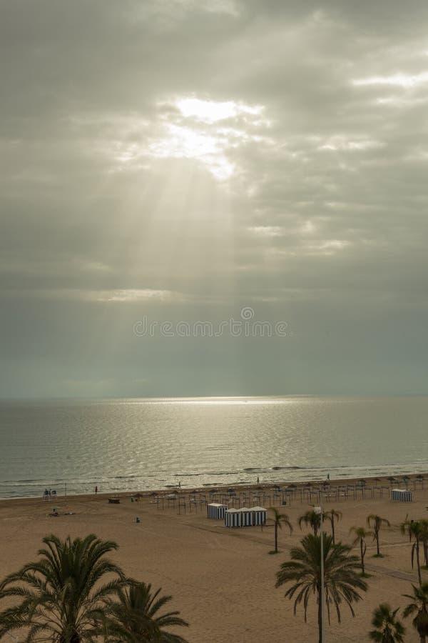 Ray of sun through the clouds lighting the horizon line between. Sky and sea stock photos