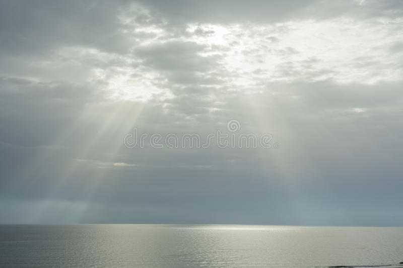 Ray of sun through the clouds lighting the horizon line between. Sky and sea stock photography