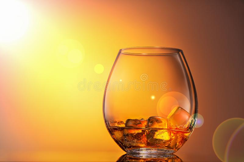 Glass of whiskey Scotch with ice on an orange background, it is illuminated by sunlight. Close up, copy space. royalty free stock image