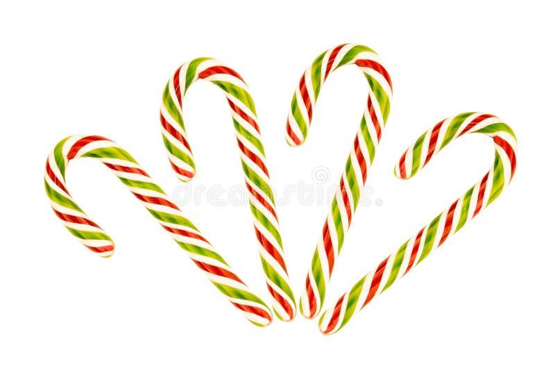 Rayas rojas verdes del caramelo del bastón de caramelo de la Navidad en los caramelos festivos de un fondo blanco fotos de archivo