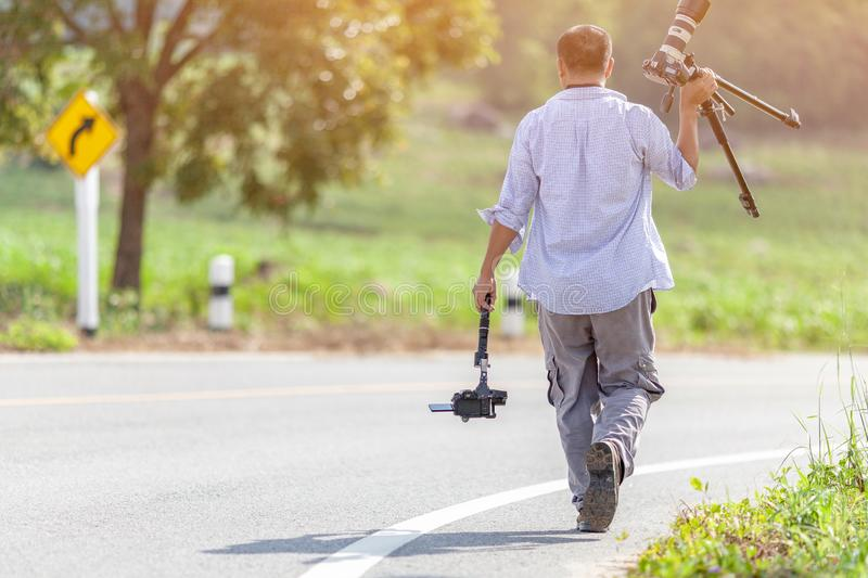 Rayong, Thailand : February 28,2019 : Behind of the Photographers holding the camera and walking on the road.selective focus. royalty free stock photos