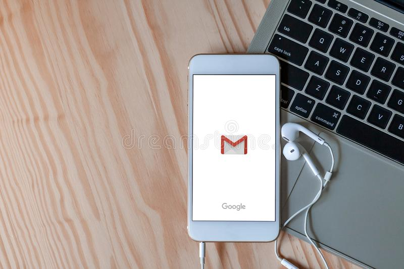 Rayong, Thailand, May 19, 2019: Gmail logo on smartphone screen placed on laptop keyboard on wood background with earphones royalty free stock images