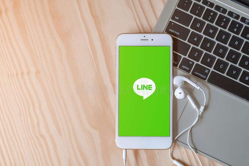 Rayong, Thailand, May 19, 2019: Line logo on smartphone screen placed on laptop keyboard on wood background with earphones royalty free stock images