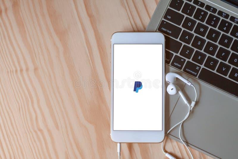 Rayong, Thailand, 19 Mei, 2019: Paypal-embleem op het smartphonescherm op laptop toetsenbord op houten achtergrond met oortelefoo stock fotografie