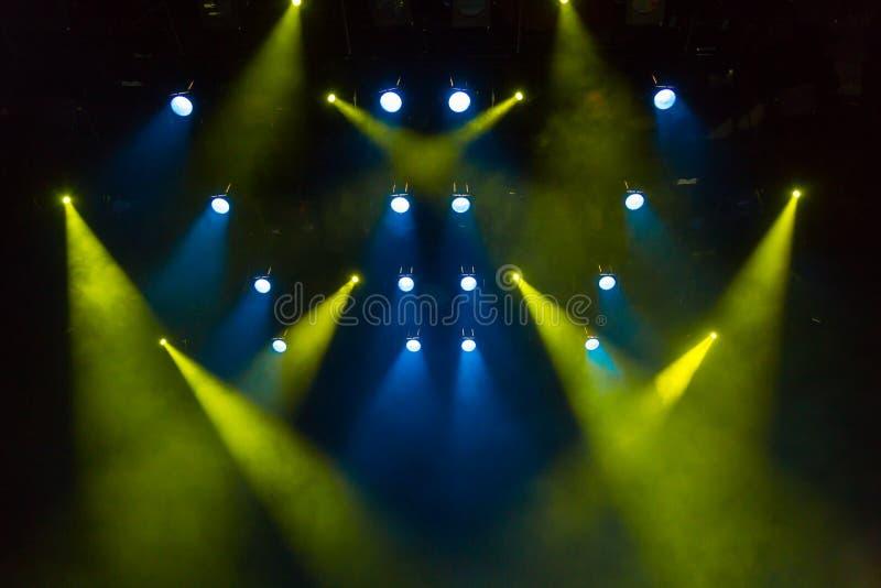 Rayons de lumière bleus et jaunes par la fumée sur l'étape Projecteur de hall de l'éclairage equipment Projecteur photo libre de droits