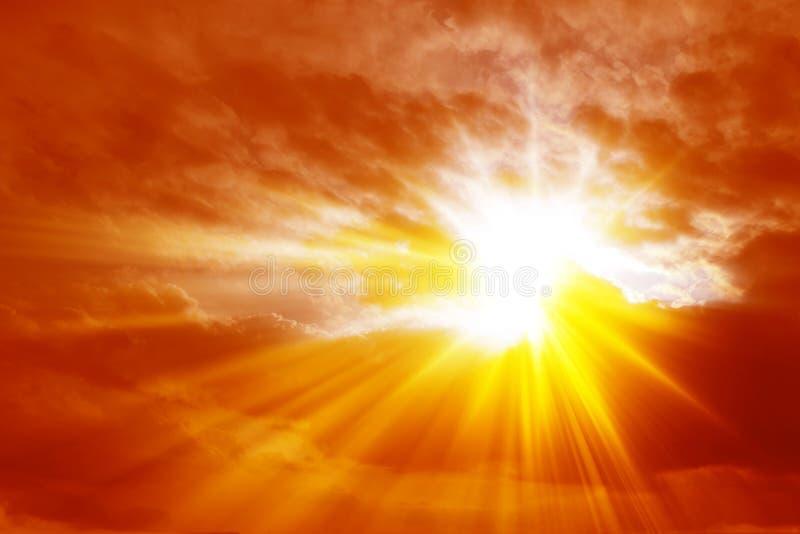 Rayons de lumière du soleil croisant les nuages dans un ciel rouge ardent photographie stock