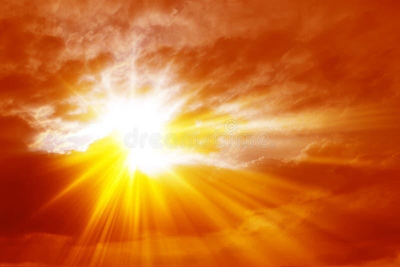 Rayons de lumière du soleil croisant les nuages dans un ciel rouge ardent image stock