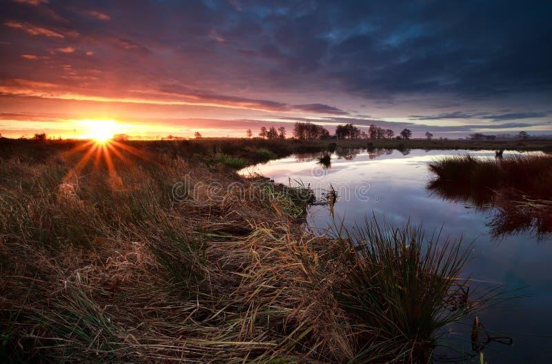 Rayons de soleil au-dessus de marais pendant le lever de soleil images libres de droits