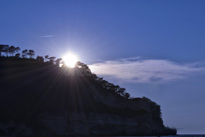 Rayons de soleil avec des arbres, des roches et des nuages photo libre de droits