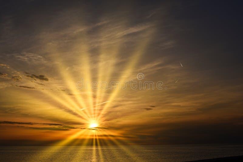 Rayons de soleil de coucher du soleil au-dessus de la mer photos stock