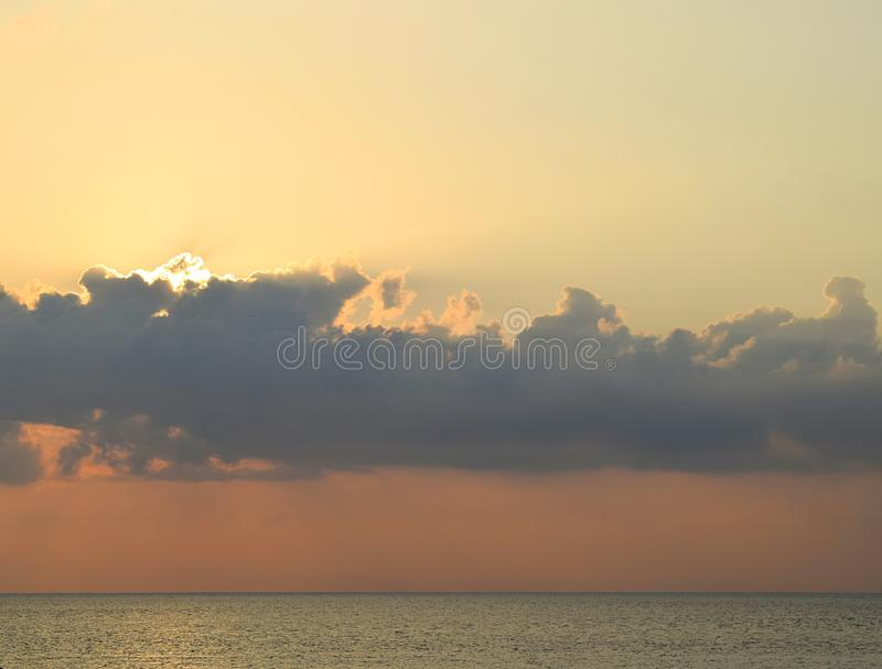 Rayons de soleil d'or lumineux par des nuages dans le ciel, l'eau de mer bleue et l'horizon - fond naturel images libres de droits