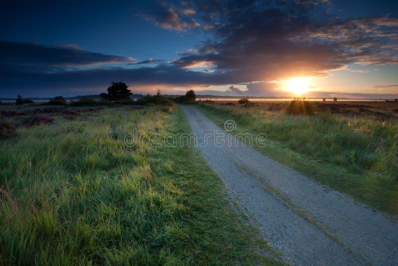 Rayons de soleil de lever de soleil au-dessus de la route moulue photo libre de droits