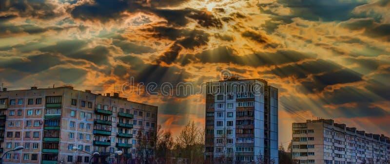 Rayons de soleil faisant leur sortie des nuages au-dessus des maisons photo libre de droits
