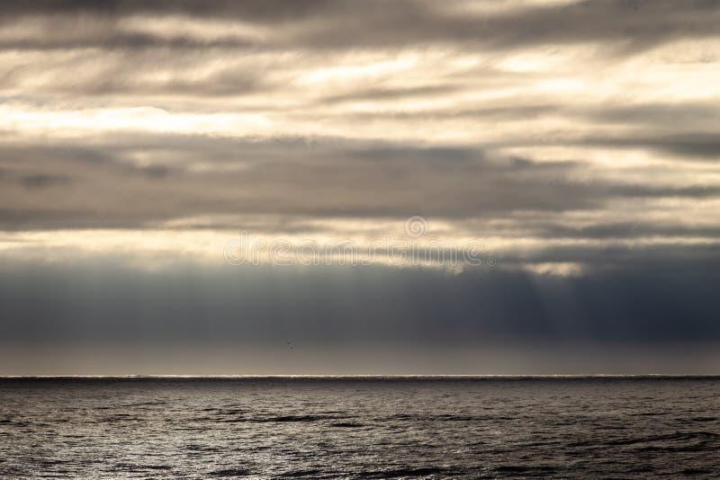Rayons de Sun par des nuages près de l'océan photographie stock libre de droits