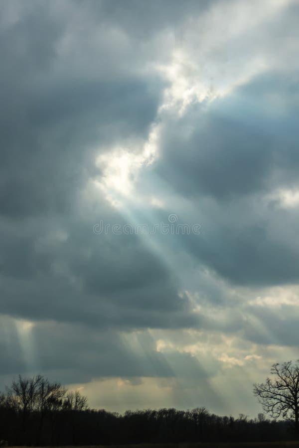 Rayons de Sun traversant les nuages un jour orageux d'hiver au crépuscule avec un contour morne des arbres sans feuilles dans le  image stock