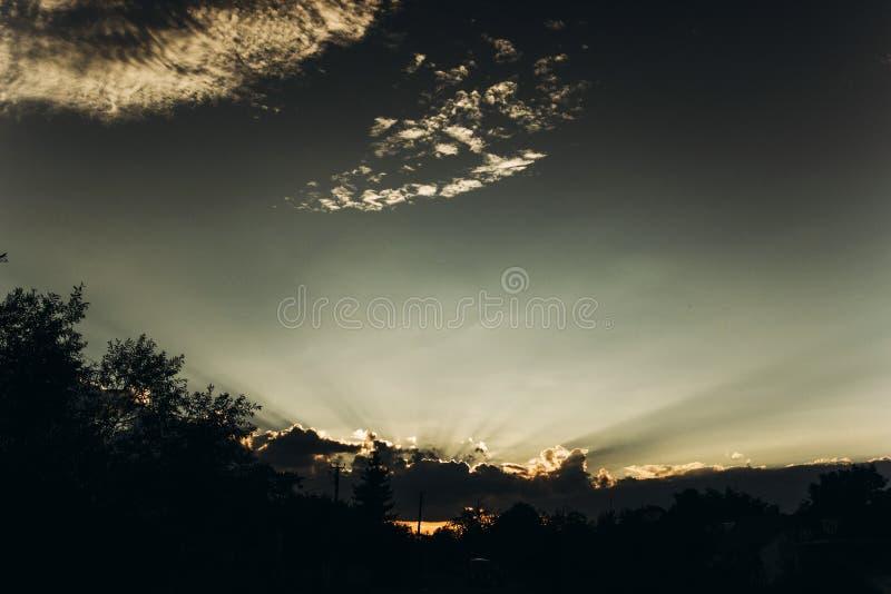 Rayons légers de beau coucher du soleil par des nuages en ciel en été Atmosphère photographie stock
