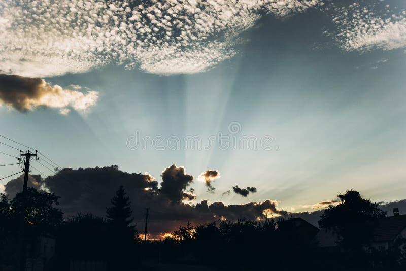 Rayons légers de beau coucher du soleil par des nuages en ciel en été Atmosphère photo stock