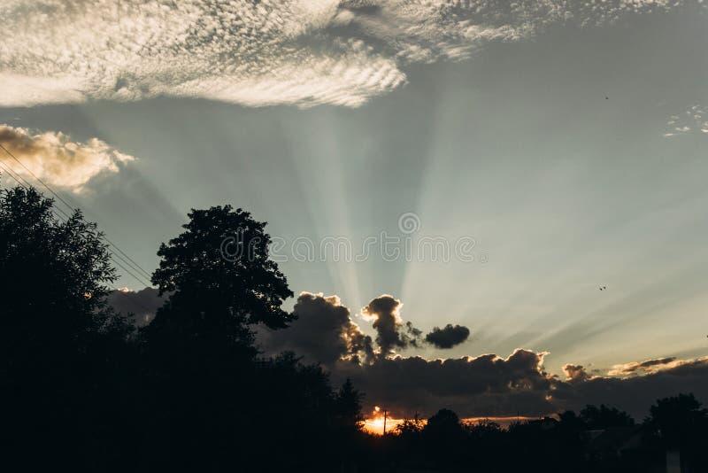 Rayons légers de beau coucher du soleil par des nuages en ciel en été Atmosphère images stock