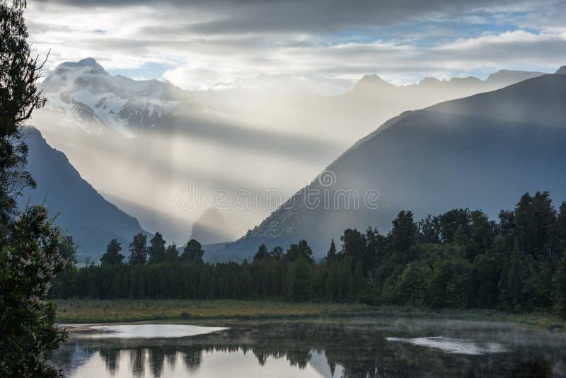 Rayons lumineux de contraste du soleil de matin au-dessus du lac Matheson photographie stock