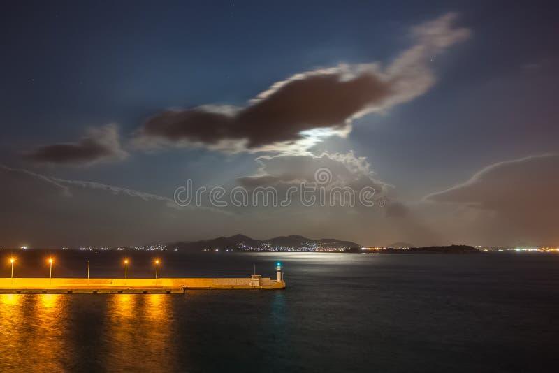 Rayos de la luna que iluminan el mar delante del puerto de Pireo fotografía de archivo