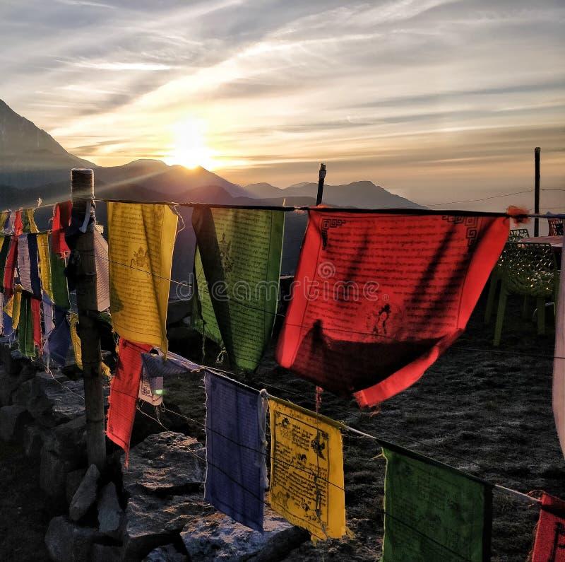 Rayos de la salida del sol que cubren la montaña y el valle con las banderas tibetian foto de archivo libre de regalías