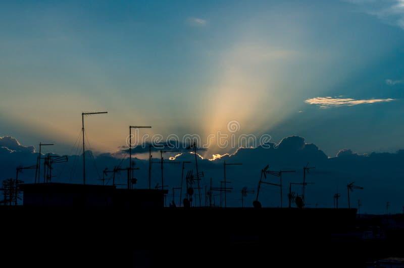 Rayos de sol detrás de las nubes en la puesta del sol con las antenas imagenes de archivo