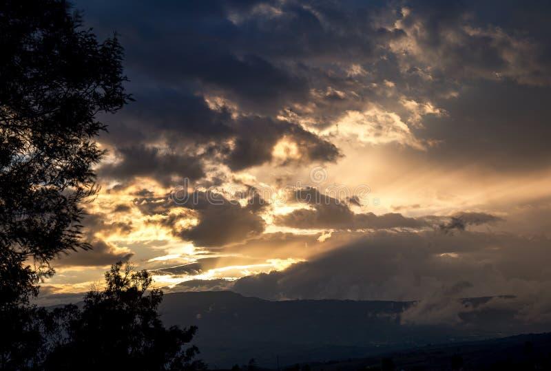 Rayos de sol hermosos que cruzan el cielo en la puesta del sol foto de archivo