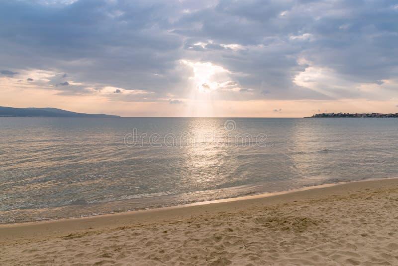 Rayos de sol o rayos del sol que miran a escondidas a través de las nubes en una salida del sol en la playa hermosa fotografía de archivo