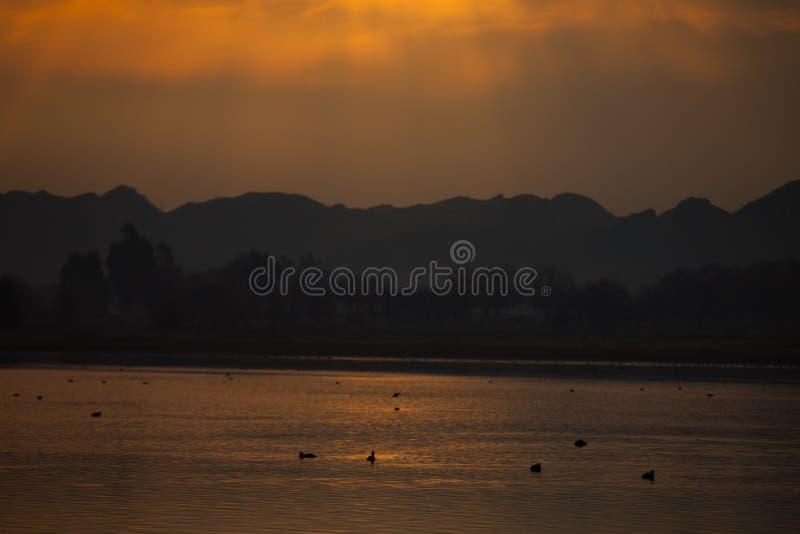 Rayos del sol en el lago en la puesta del sol fotos de archivo