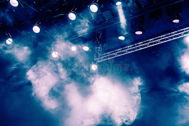 Rayos ligeros azules del proyector a través del humo en el teatro o la sala de conciertos Equipo de iluminación para un funcionam imagen de archivo