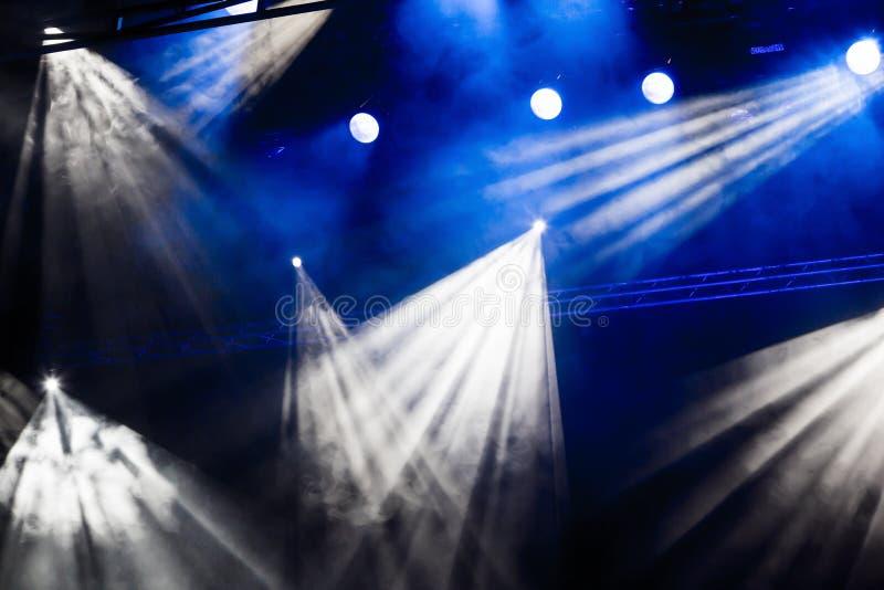 Rayos ligeros blancos y azules del proyector a través del humo en el teatro o la sala de conciertos Reflector del pasillo de la i fotografía de archivo