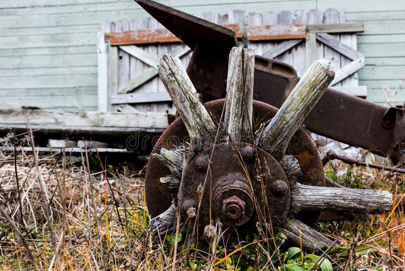 Rayos rotos tractor automotriz antiguo y eje de madera de la rueda del vintage cubiertos en moho imagen de archivo