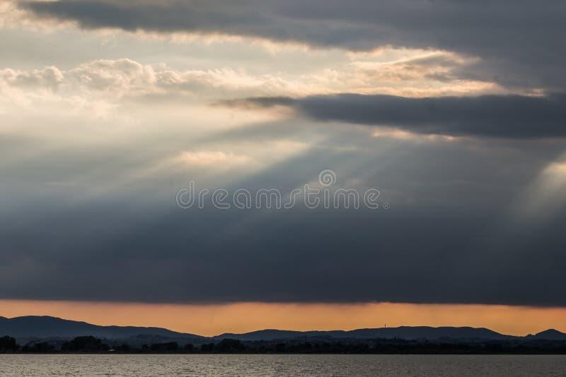 Rayos solares en la puesta del sol cercana, con las nubes oscuras en el fondo, un cielo anaranjado, y el lago Umbría, Italia Tras fotos de archivo
