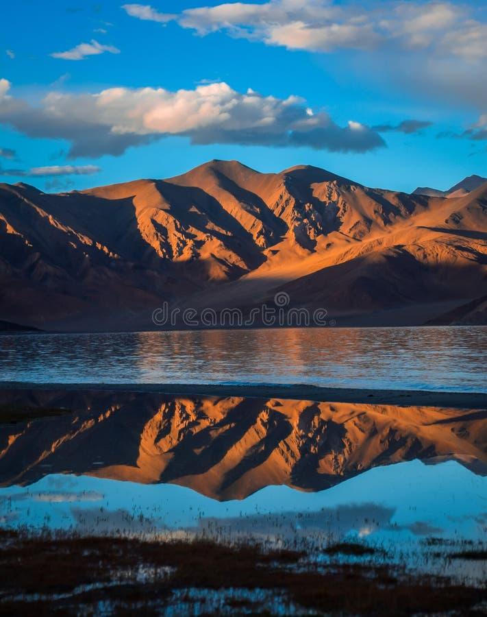rayos solares en las montañas y lago que refleja sobre la opinión panorámica del agua foto de archivo
