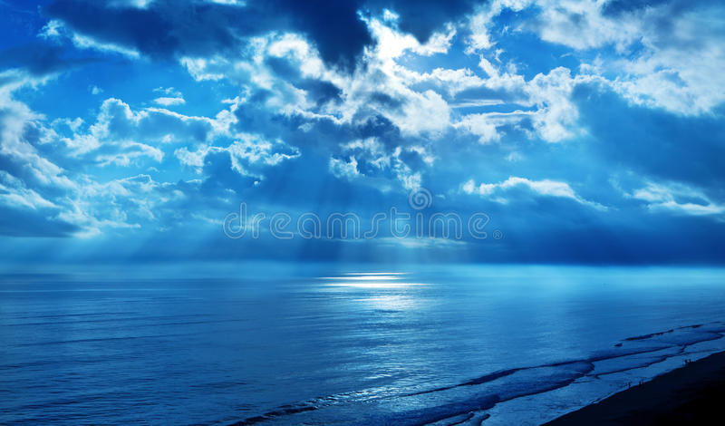 Rays Clouds Blue Sky Ocean. A blue sky with the suns rays shining on the ocean