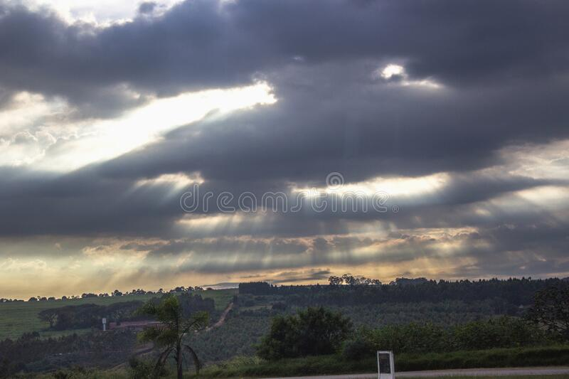 The rays between the clouds. From the bus window, this beautiful view of the sky with its rays of light passing between the clouds . in the distance you can see royalty free stock photo