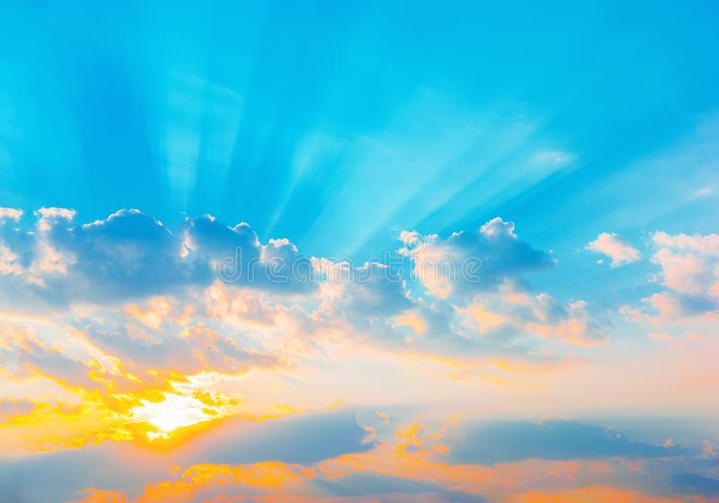 Rays dramatisk blå himmel för soluppgång med den orange solen avbrott till och med molnen mot bakgrund field blåa oklarheter för  arkivbilder