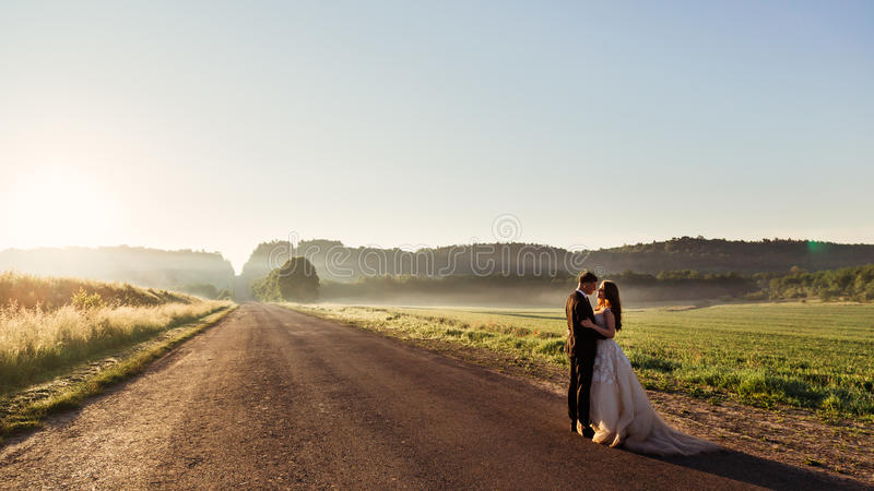 Rays of evening light cover road where wedding couple stands royalty free stock photography