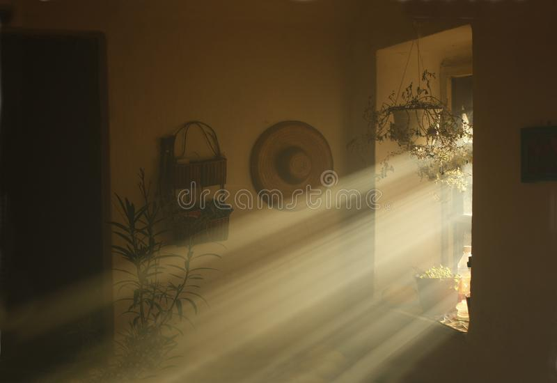 Rays of light coming from a window in an old country house. Heavenly light in a dusky old house royalty free stock images