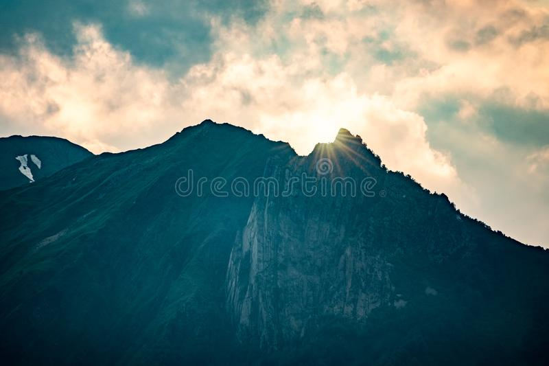 Rays of the setting sun over a high green mountain with rocks and snow on top royalty free stock images