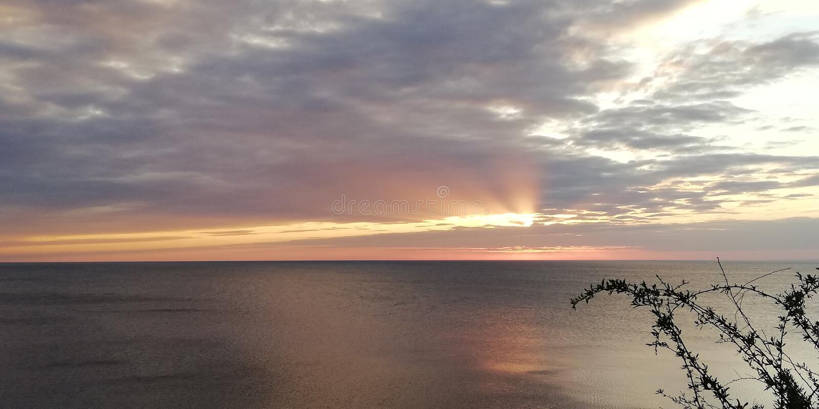 The rays of the sun through the clouds. An interesting atmospheric phenomenon. Sunset seascape. Bright background. The autumn severe dark sea is illuminated by royalty free stock photos