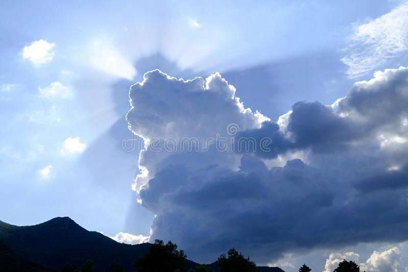The rays of the sun in the sky shining from behind the clouds 2 stock photo