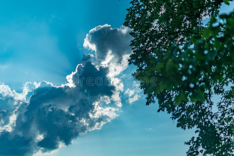 Rays of sunlight break through a back-lit cloud against a blue sky on a beautiful summer`s day with bokeh foliage in the stock photography