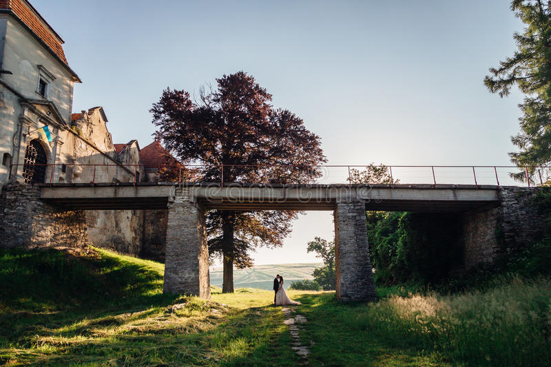 Rays of sunlight illuminate lonely wedding couple. Standing under the bridge stock images