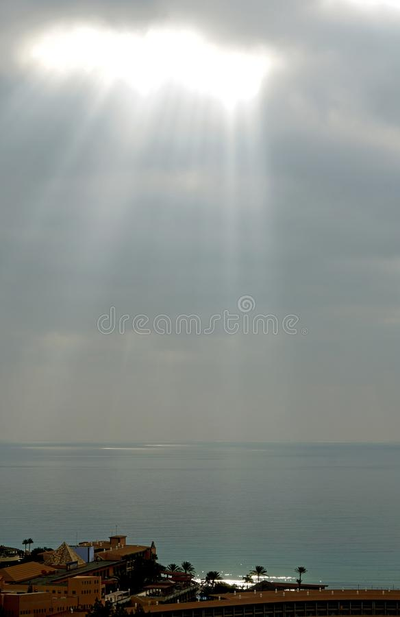 The rays of sunlight make their way through the clouds. The sun is above the ocean. A bright gloss on the surface of the water. Space above the Atlantic. Ocean stock images