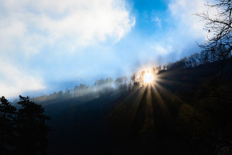 Sunbeams coming over mountain on foggy morning in Alps royalty free stock photography